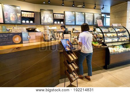 SEOUL, SOUTH KOREA - CIRCA MAY, 2017: woman at Starbucks in Seoul. Starbucks Corporation is an American coffee company and coffeehouse chain.