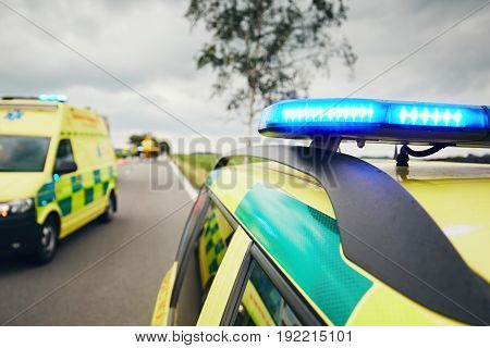 Ambulance cars. Teams of the Emergency medical service are responding to an traffic accident in bad weather.