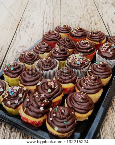 Chocolate Cupcakes. Homemade decorated chocolate cupcakes on a black serving tray with rustic background