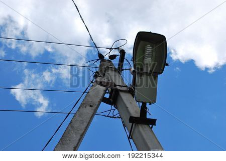 Electric pole and lamp, against a blue sky background