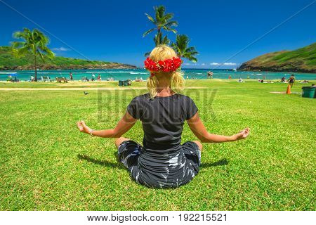 Serene meditation yoga. Woman meditating on Hawaiian palm beach in black sarong with red hawaiian lei on her head. Female contemplates ocean in popular Hanauma Bay Nature Preserve, Oahu, Hawaii, USA.