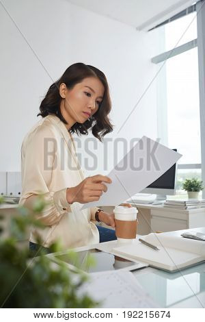 Serious young Vietnamese businesswoman reading document at office