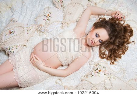 Beautiful pregnant woman with luxurious hair black lying on the couch. Top view.