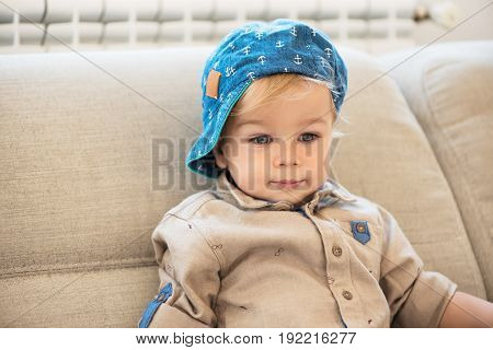 Portrait Of Nicely Dressed Little Boy With Blue Eyes Sitting On The Sofa.