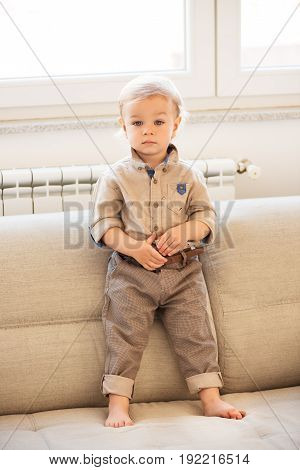Nicely Dressed Little Boy With Blue Eyes Standing Up On The Sofa.
