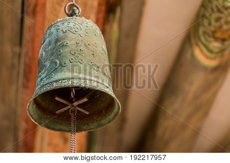 Closeup of an old brass bell hanging from a wooden roof of an old temple in Korea