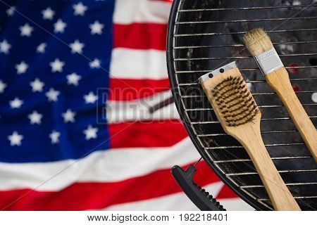 Close-up of basting brush arranged on barbeque against American flag