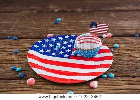 Independence day cupcake on patriotic plate on wooden table