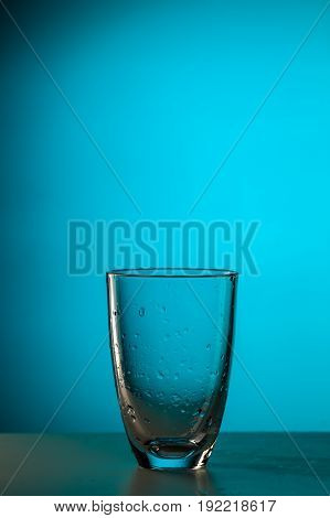 Empty clean glass on blue background, photo in studio