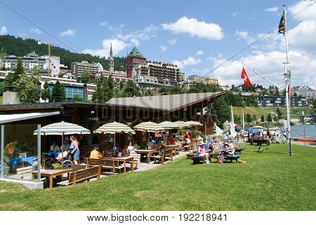 People Eating And Sunbathing At A Restaurant At St. Moritz