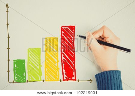 Human hand with pencil colorful graph on wall background