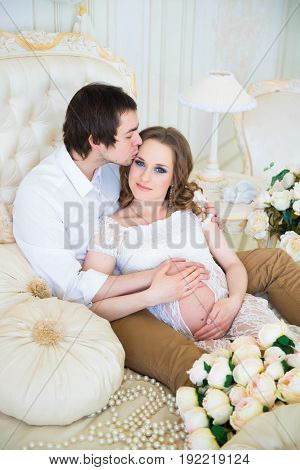 Beautiful couple, pregnant young woman and man hugging with love kisses, sitting on the bed, in a home interior