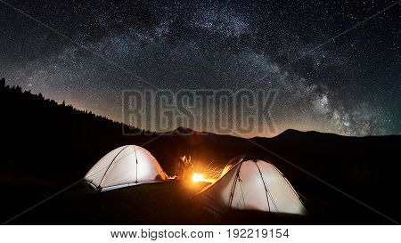 Night Camping. Couple Tourists Sitting And Hugging At A Campfire Near Two Illuminated Tents Under Be