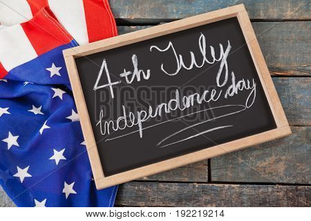 Close-up of American flag and slate with text 4th july independence day