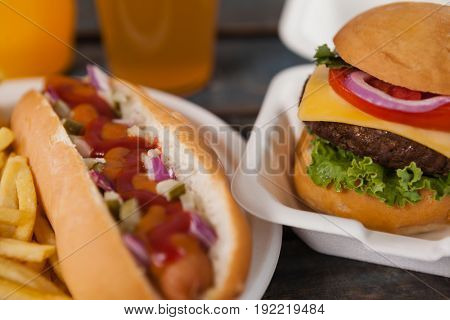 Close-up of hot dog and hamburger on wooden table