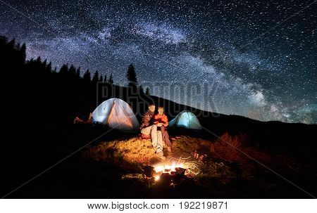 Night Camping In The Mountains. Couple Tourists Sitting At A Campfire Near Two Illuminated Tents Und