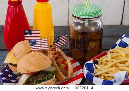Close-up of snacks and cold drink on wooden table with 4th july theme