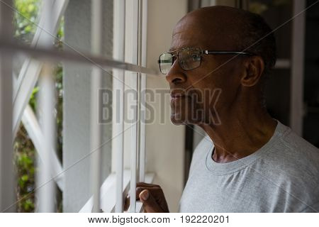 Thoughtful senior man wearing eyeglasses while looking out through window at home