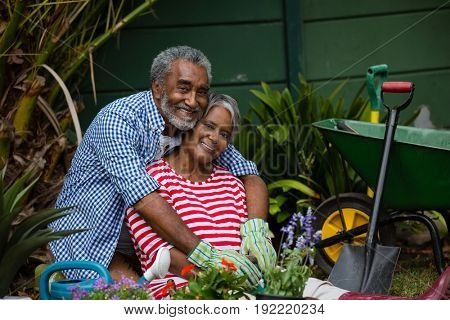 Portrait of happy senior couple embracing by plants in backyard