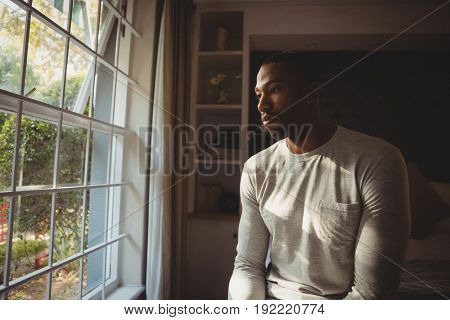 Thoughtful man sitting by window in bedroom at home