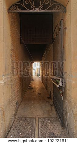 old brick wall and pave way and old door lead into narrow alley/ alley