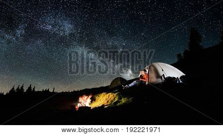 Night Camping. Man And Woman Tourists Sitting In The Illuminated Tent Near Campfire Under Amazing Ni