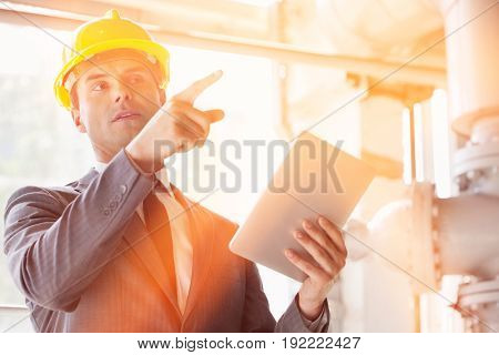 Young male engineer with digital tablet pointing away in industry