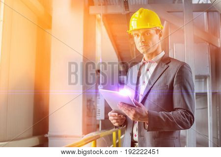 Portrait of confident male architect holding digital tablet in industry