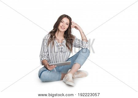 attractive brunette woman using digital tablet and sitting on floor isolated on white