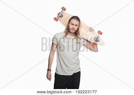 Young Skeptical Man Holding Longboard And Looking At Camera Isolated On White