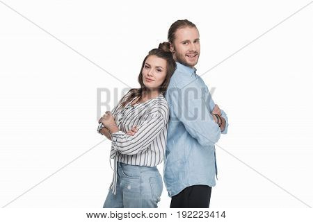 Happy young couple standing back to back and smiling at camera