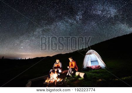 Night Camping In The Mountains. Man And Woman Tourists Have A Rest At A Campfire Near Illuminated Te