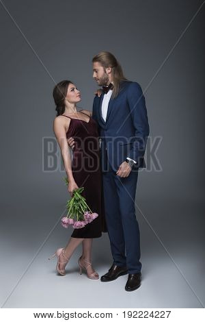 Young Elegant Sweethearts In Evening Fashion Outfit Standing Together With Bouquet Of Flowers