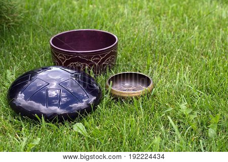 singing bowls and steel tongue drum on the grass