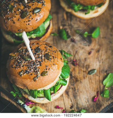 Healthy vegan burgers with beetroot and quinoa patty, arugula, avocado sauce, wholegrain bun on rustic wooden board over dark background, selective focus, copy space, square crop. Detox food concept