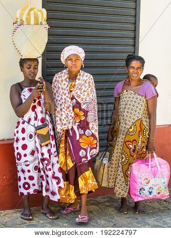 Antsiranana Madagascar - December 20 2015: Unidentified Madagascar women in colorful clothes on the street of Antsiranana (Diego Suarez) Madagascar Africa. Woman carries her little baby on her back and carry bag on their heads.