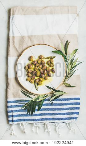 Pickled green Mediterranean olives in natural virgin olive oil on white ceramic plate and olive tree branch over grey marble background, top view