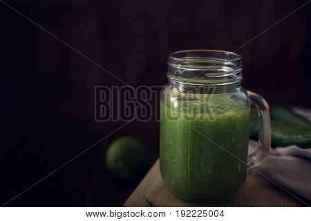 Healthy green smoothie on a wooden table with copy space