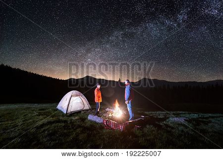 Night Camping. Couple Tourists Standing At A Campfire Near Illuminated Tent Under Beautiful Night Sk