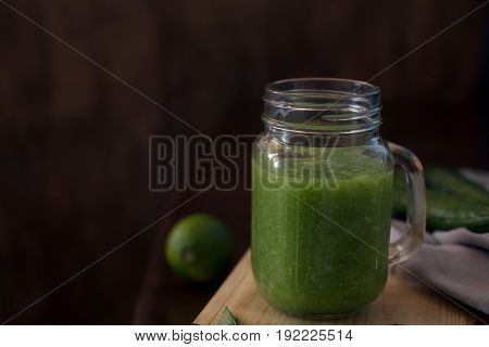 Healthy green smoothie on a wooden table with