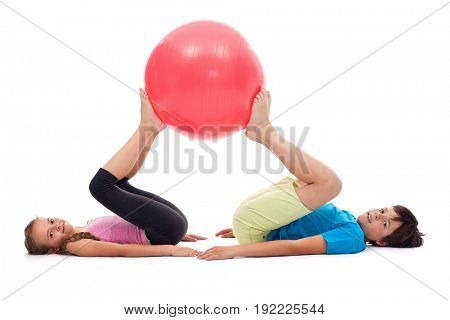 Young kids exercising with large gymnastic rubber ball - strengthening cooperation skills