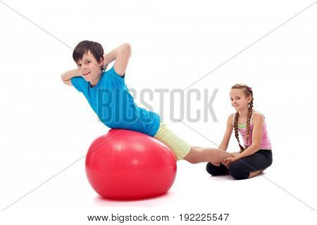 Kids helping each other exercising with a large gymnastic rubber ball - isolated