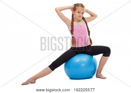 Little girl sitting on large gymnastic rubber ball exercising - balance and stretching