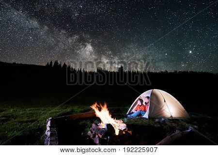 Night Camping In The Mountains. Romantic Couple Tourists Sitting In The Illuminated Tent Near Campfi