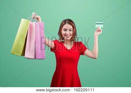Santa asian woman holding shopping bags and credit card against blue vignette