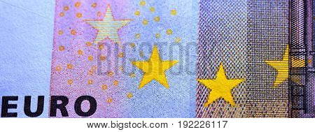 Macro photograph of the observe of a fifty euro bill showing yellow stars and the word euro