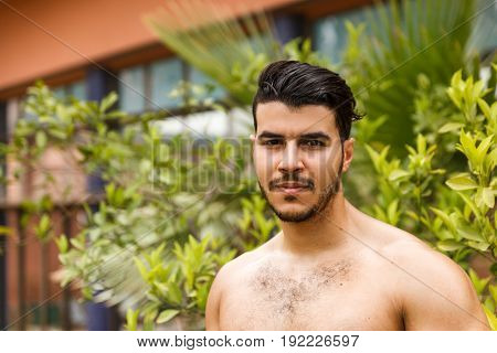 Handsome shirtless man in the park in the summer sunny day