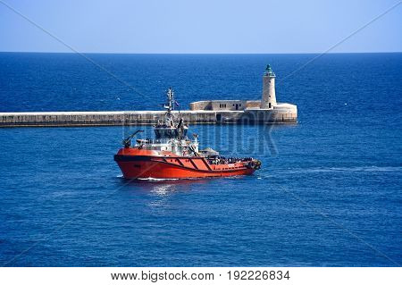 VALLETTA, MALTA - MARCH 30, 2017 - Tug boat in the Grand Harbour with the lighthouse to the rear Valletta Malta Europe, March 30, 2017.