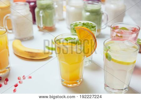 Glasses of cold refreshing drink with fruits and ice on a table. Summer lemonade.