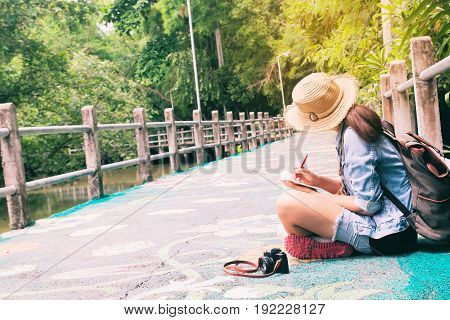 Young asian woman traveling and writing on notebook against beautiful tropical scenery